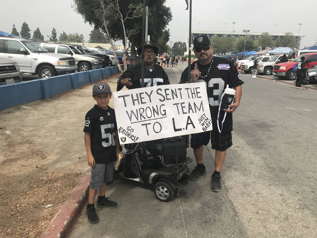Javier Yi, right, a longtime Raiders fan, holds sign before Raiders played the Rams in Los Angeles on Saturday. (Gilbert Manzano)