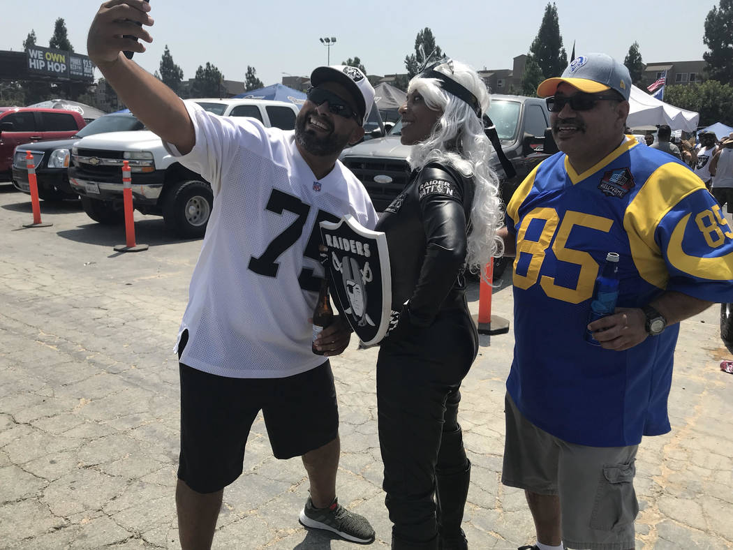 Faith Turner, center, who goes by Raider Storm, accepts photo request from football fans before Raiders-Rams game in Los Angeles. (Gilbert Manzano)