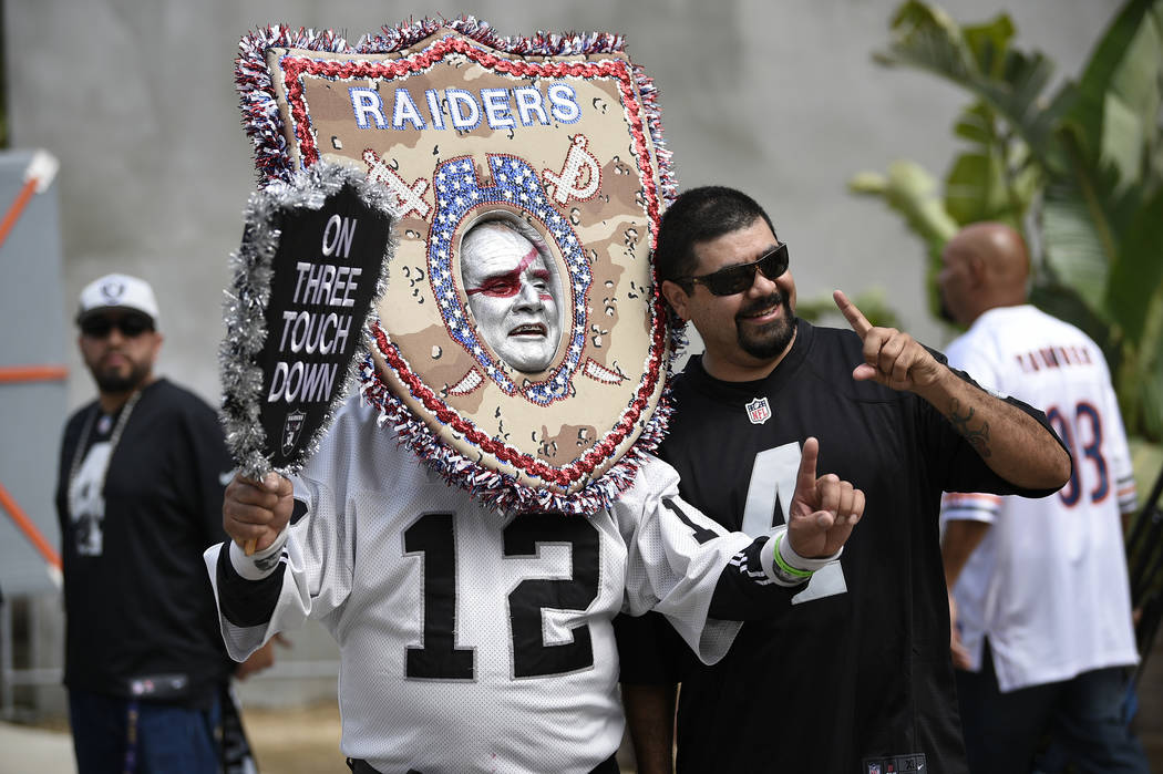 Oakland Raider fans pose before an NFL preseason football game against the Los Angeles Rams Saturday, Aug. 18, 2018, in Los Angeles. (AP Photo/Kelvin Kuo)