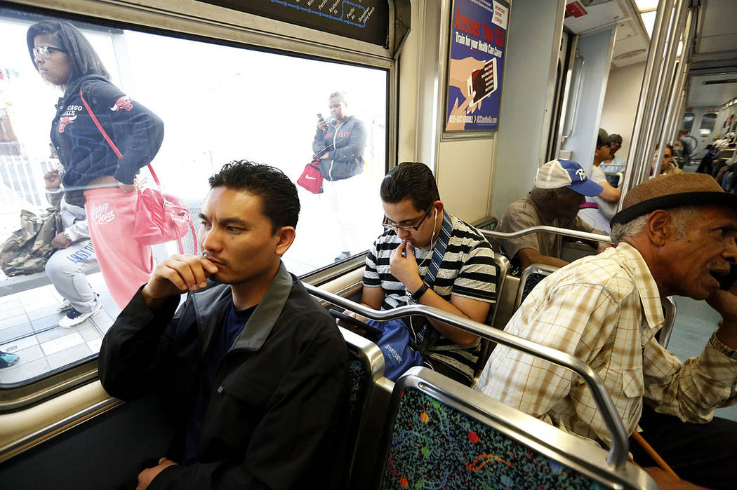 Phal Sok, left, rides the Metro Blue Line train in Los Angeles to visit with his brother in Long Beach, Calif., in 2017. (Genaro Molina/Los Angeles Times via AP)