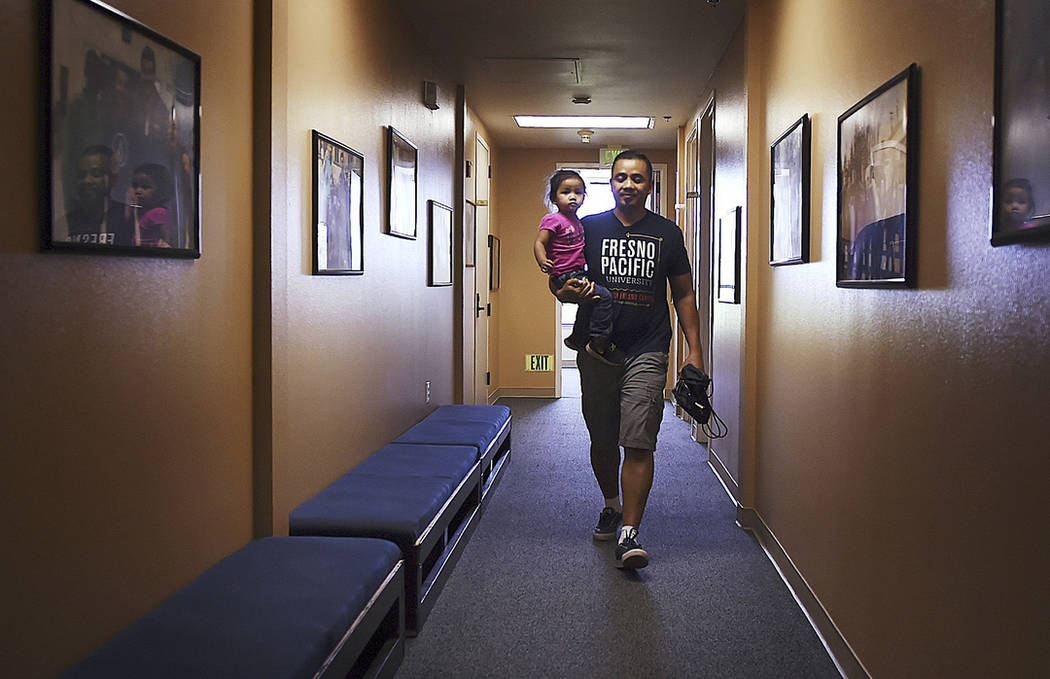 Vanna In carries his daughter Thanny in Fresno, Calif., in May 2018. (Eric Paul Zamora/The Fresno Bee via AP)