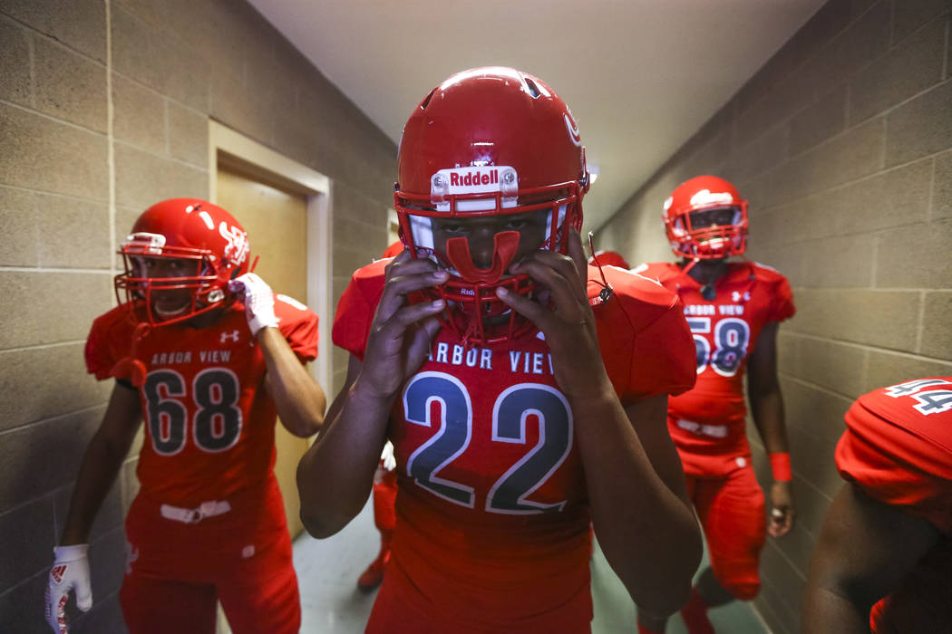 Arbor View Aggies defensive end Zavier Alston (22) puts on his helmet in the locker room before playing the Valley View Eagles of California in a varsity football game at Arbor View High School in ...