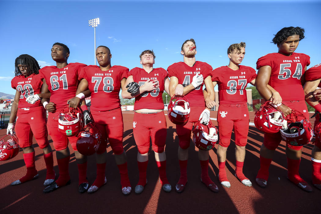 The Arbor View Aggies embrace in unity during the national anthem before playing the Valley View Eagles of California in a varsity football game at Arbor View High School in Las Vegas on Friday, A ...