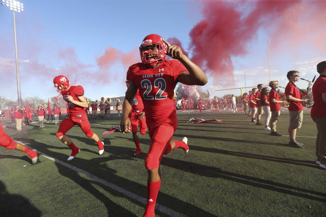 Arbor View Aggies defensive end Zavier Alston (22) and his team hit the field before playing the Valley View Eagles of California in a varsity football game at Arbor View High School in Las Vegas ...