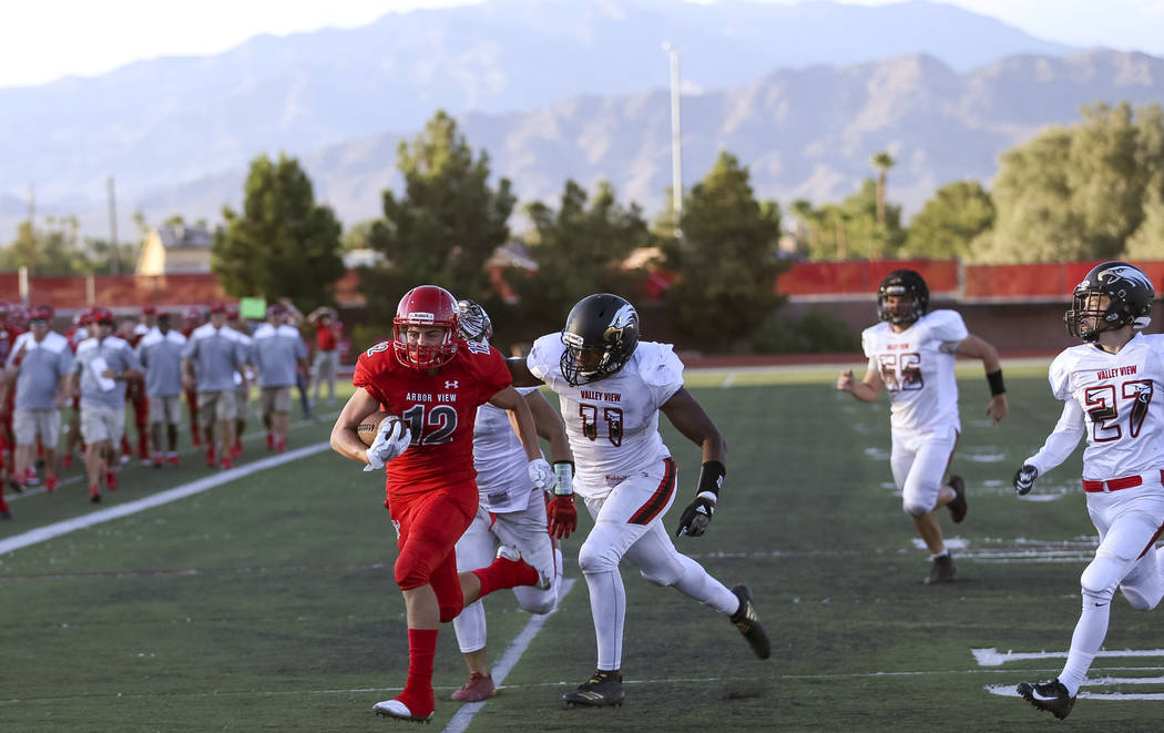 Arbor View Aggies defensive back Hayden Stimpson (12) runs past Valley View Eagles linebacker Ramon Clark (11) for a touchdown during the second half of a varsity football game at Arbor View High ...
