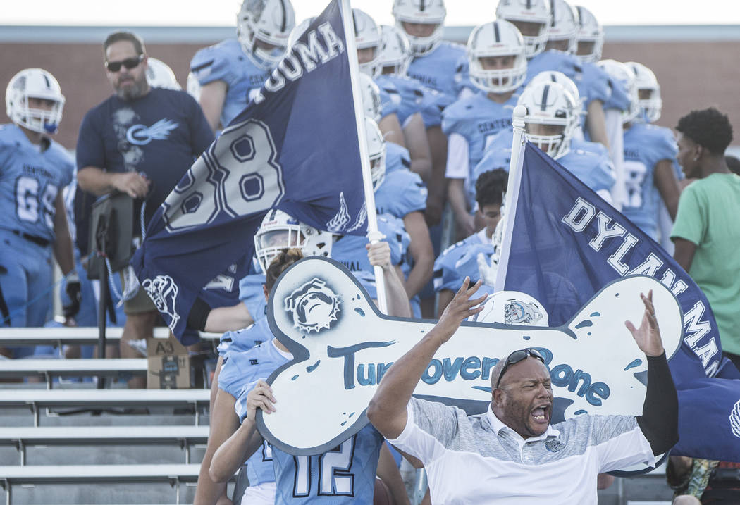 Centennial Stan Standifer, bottom/right, leads the Bulldogs onto the field before the start of their home matchup with Sierra Vista High School on Friday, Aug. 17, 2018, at Centennial High School, ...