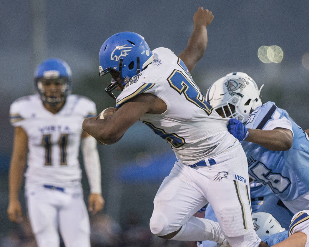Sierra Vista senior running back Bryan LaGrange (28) attempts to break the tackle of Centennial junior defensive tackle Thomas Lane (56) in the first quarter on Friday, Aug. 17, 2018, at Centennia ...