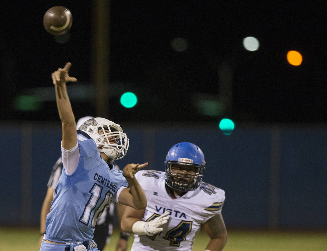 Centennial sophomore quarterback Colton Tenney (10) throws on the run with Sierra Vista senior defensive lineman Elijah Tialavea (44) in pursuit in the second quarter on Friday, Aug. 17, 2018, at ...
