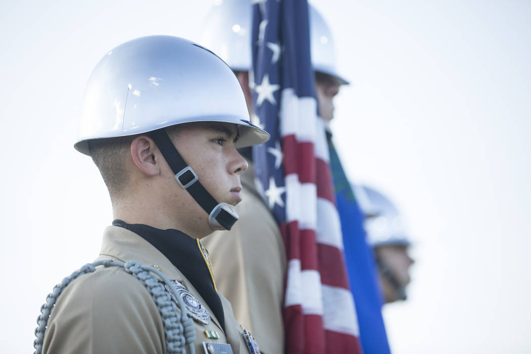 Centennial honor guard member Ryan Mull, left, waits to present the colors before the start of the Bulldogs home matchup with Sierra Vista on Friday, Aug. 17, 2018, at Centennial High School, in L ...