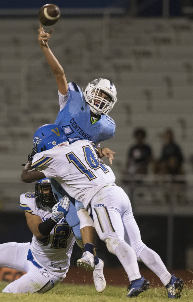 Centennial sophomore quarterback Colton Tenney (10) gets hit as he throws by Sierra Vista freshman safety receiver D'Andre Washington (14) in the fourth quarter on Friday, Aug. 17, 2018, at Centen ...