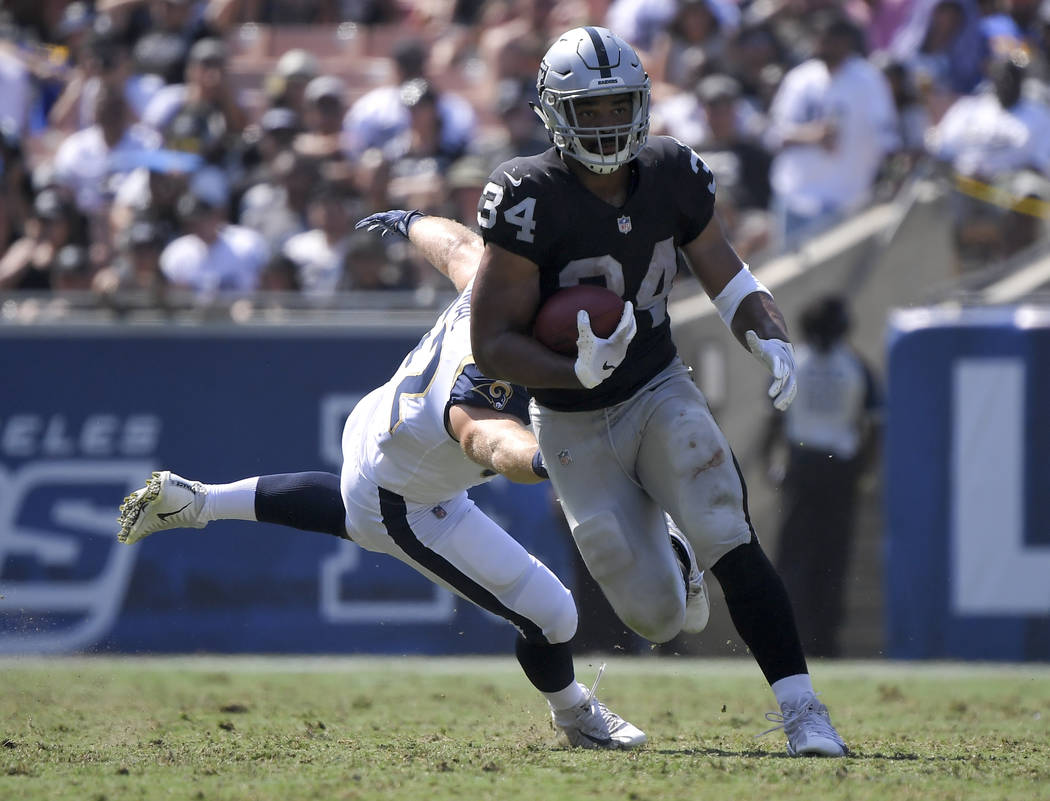 Oakland Raiders running back Chris Warren runs past Los Angeles Rams defensive end Brian Womac during the second half in an NFL preseason football game Saturday, Aug. 18, 2018, in Los Angeles. (AP ...