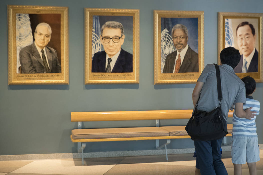 Gen Goto, left, of Tokyo, and his son Motoharu Goto, 9, pause in front of a portrait of former United Nations Secretary-General Kofi Annan during a visit to U.N. headquarters, Saturday, Aug. 18, 2 ...