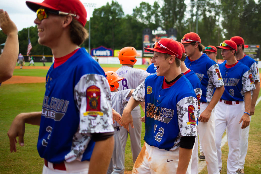 Logan LaCourse of Midland, Mich., Berryhill Post 165 laughs as he high fives a batboy after the team took down Las Vegas, Nev., Post 40 3-2 in game seven of The American Legion World Series at Vet ...