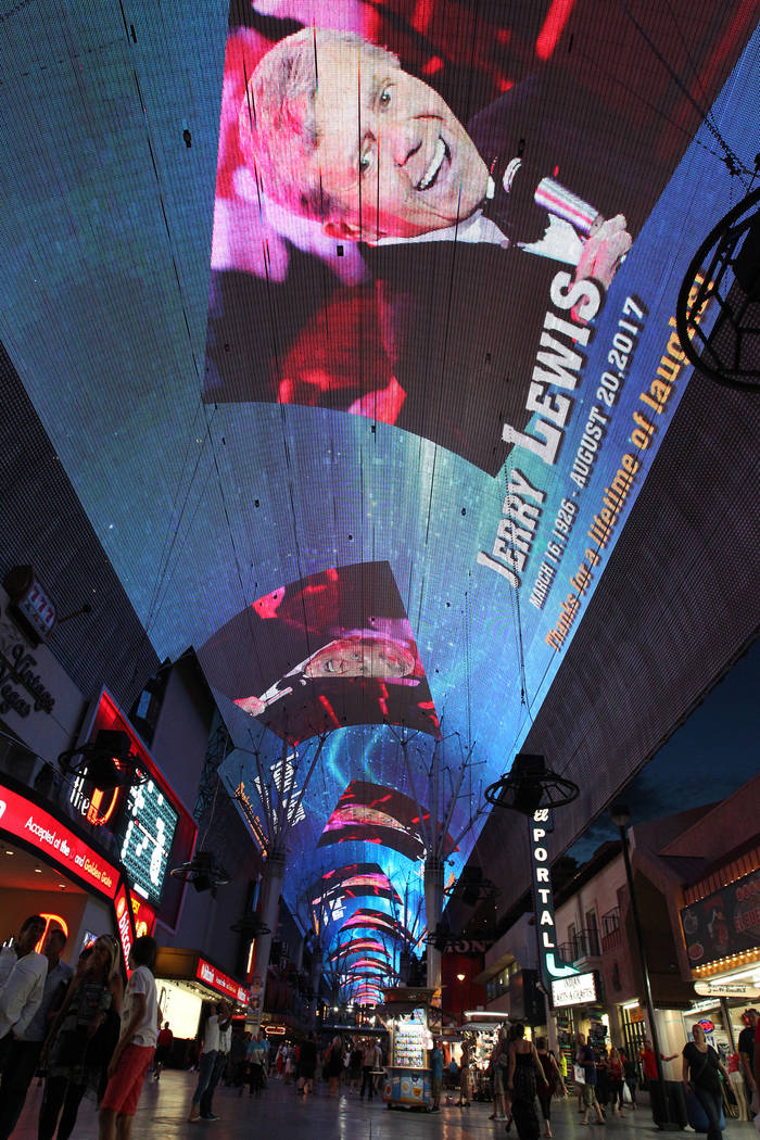 People watch a tribute to legendary entertainer and humanitarian Jerry Lewis on the Viva Vision screen at Fremont Street Experience in downtown Las Vegas Monday, Aug. 21, 2017. A video tribute als ...
