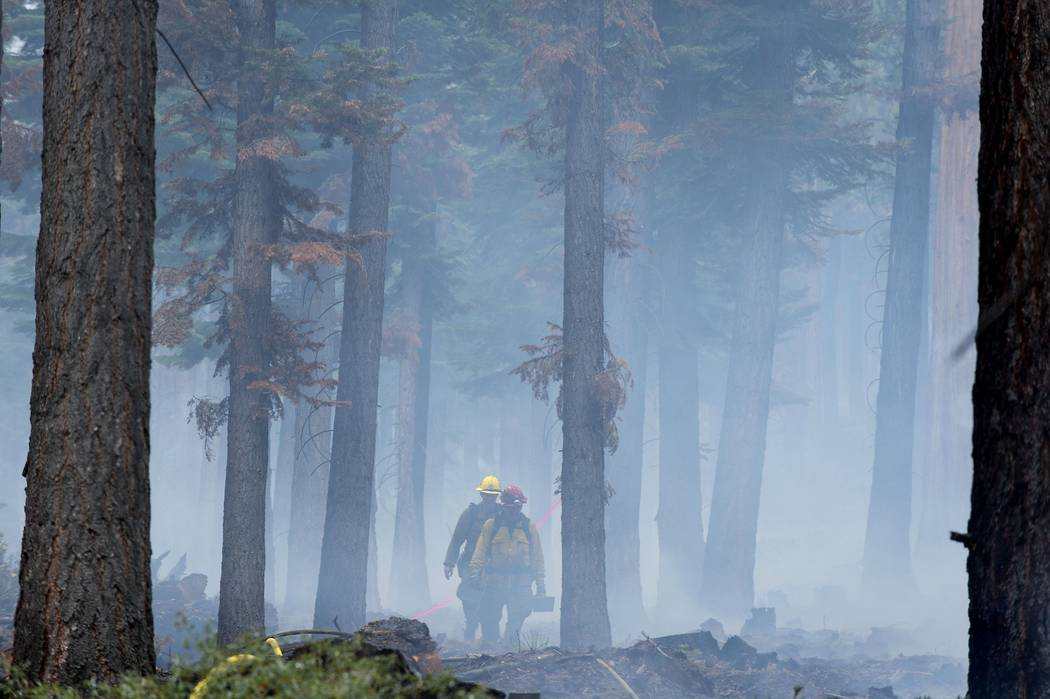 Fire crews work on the Emerald Fire along California Highway 89, Friday, Oct. 14, 2016 on the southwest shores of Lake Tahoe. (Randall Benton/The Sacramento Bee via AP)