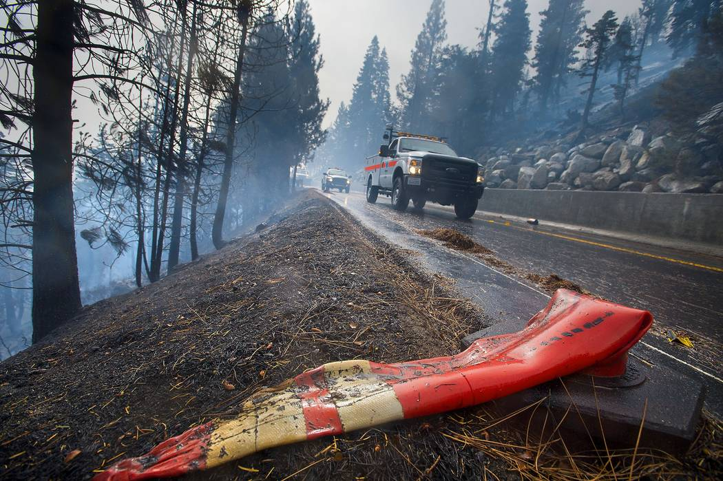 CalTrans road crews drive past a melted traffic cone at the Emerald Fire along Highway 89, Friday, Oct. 14, 2016 on the southwest shores of Lake Tahoe. (Randall Benton/The Sacramento Bee via AP)