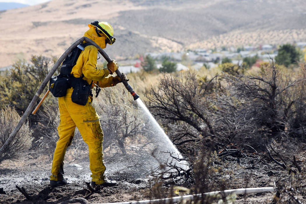 A firefighter hoses down the area on Mount Rose Highway and Edmonton Drive, Friday, Oct. 14, 2016 in Reno. (Mike Higdon/The Reno Gazette-Journal via AP)