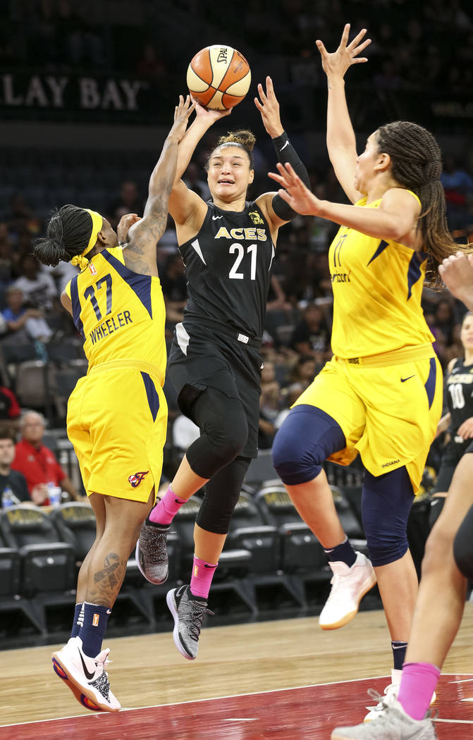 Las Vegas Aces guard Kayla McBride (21) takes a shot through Indiana Fever guard Erica Wheeler (17) and Fever forward Natalie Achonwa (11) during the first half of a WNBA basketball game at the Ma ...