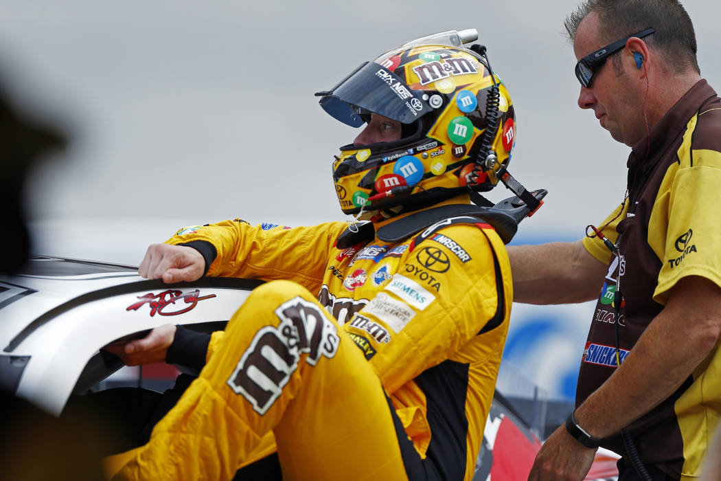 Kyle Busch climbs into his car during practice for a NASCAR Cup Series auto race, Friday, Aug. 17, 2018, in Bristol, Tenn. (AP Photo/Wade Payne)
