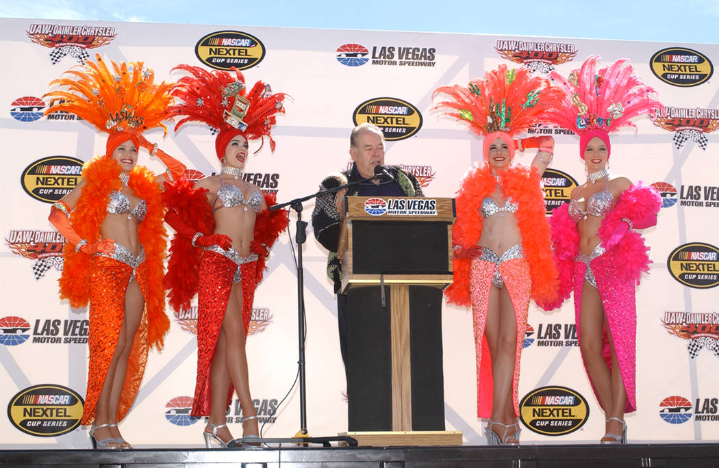 2004 March 07 | Sunday: Robin Leach is flanked by the Las Vegas Showgirls during pre-race for the 7th Annual UAW-Daimler Chrysler 400 NASCAR Nextel Cup Series event at the Las Vegas Motor Speedway ...