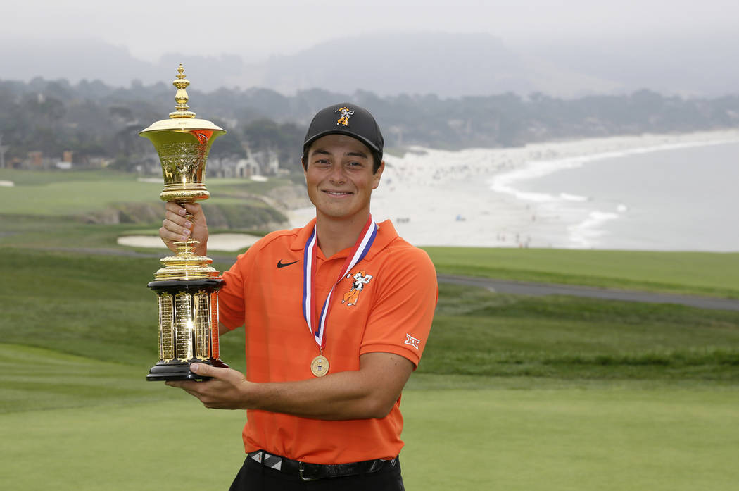 Viktor Hovland, of Norway, poses with the Havemeyer Trophy on the 13th green of the Pebble Beach Golf Links after winning the USGA Amateur Golf Championship Sunday, Aug. 19, 2018, in Pebble Beach, ...
