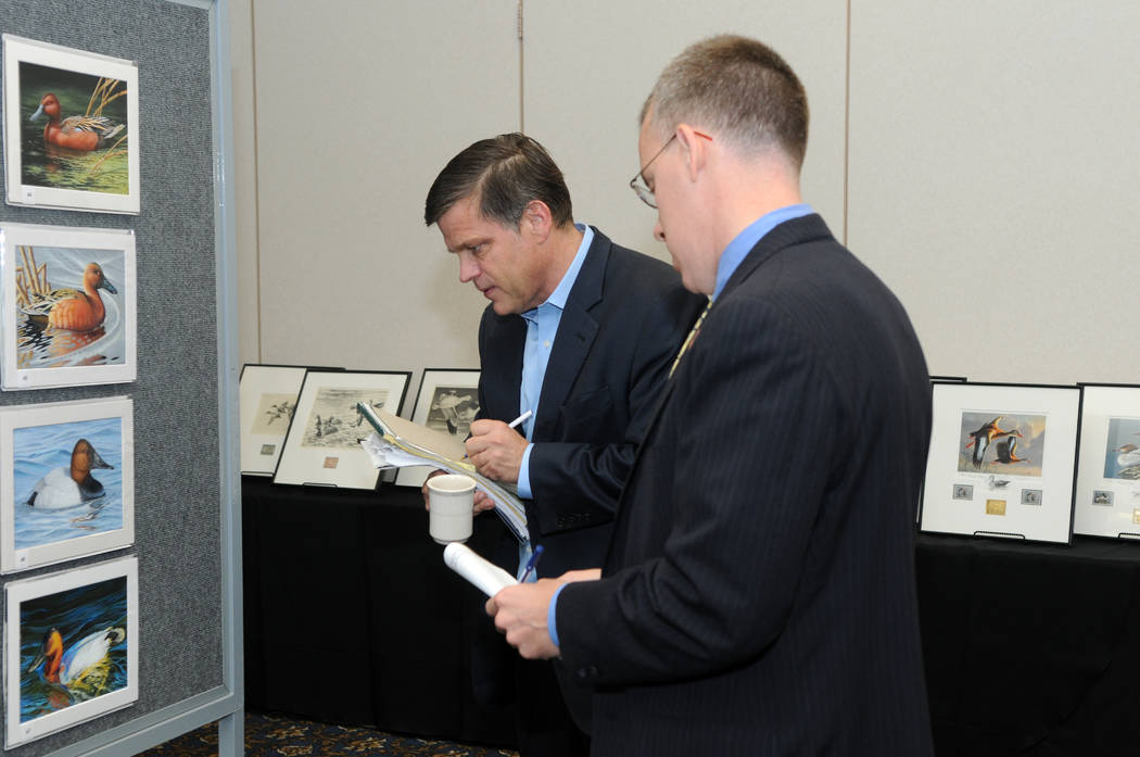 Federal Duck Stamp Contest judges Douglas Brinkley, left, and Chad Snee study the entries during the 2013 competition in Ohio. (U.S. Fish and Wildlife Service)