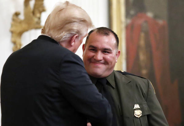 President Donald Trump, left, greets Customs and Border Patrol agent Adrian Anzaldua, during an event to salute U.S. Immigration and Customs Enforcement (ICE) officers and U.S. Customs and Border ...