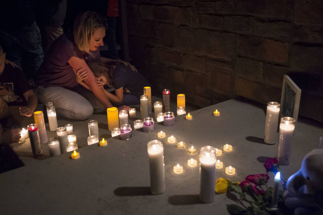 Jeanna Dietz hugs her daughter Eva, 7, while looking onto memorial on the front porch while others gather for a candlelight vigil for Shanann Watts and her two daughters, Bella, 4, and Celeste, 3, ...