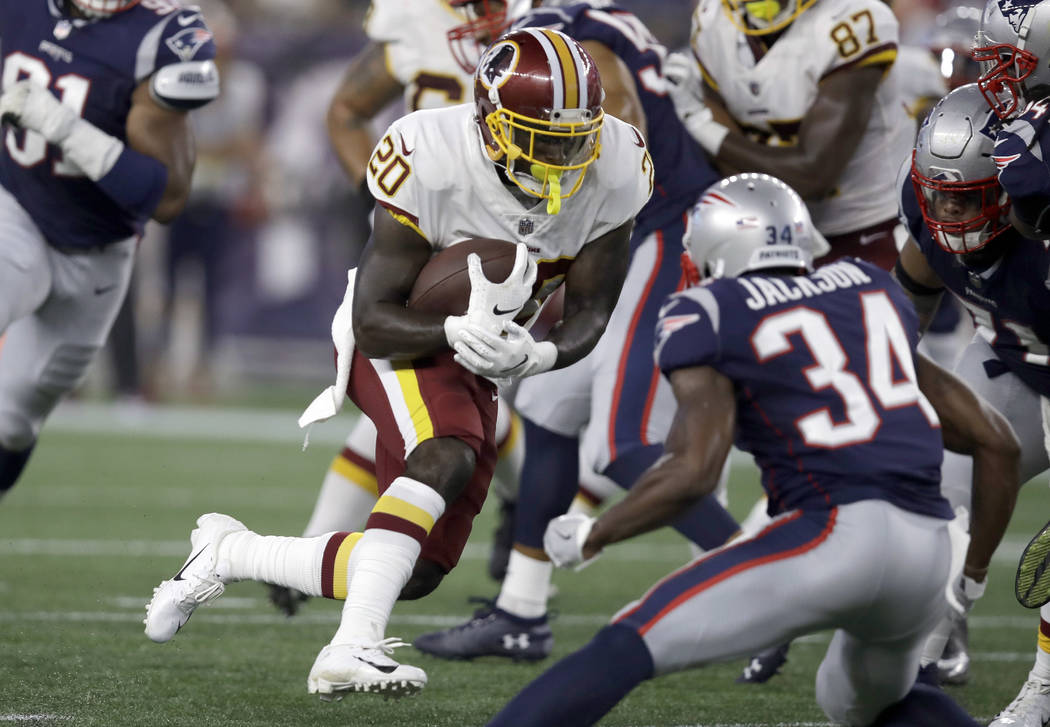 In this Aug. 9, 2018, file photo, Washington Redskins running back Rob Kelley (20) runs from New England Patriots defensive back J.C. Jackson (34) during the first half of a preseason NFL football ...