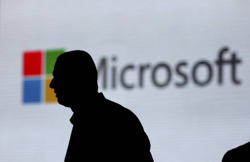 In this Nov. 7, 2017, file photo, a man is silhouetted as he walks in front of Microsoft logo at an event in New Delhi, India. Microsoft says it's uncovered new Russian hacking attempts targetin ...