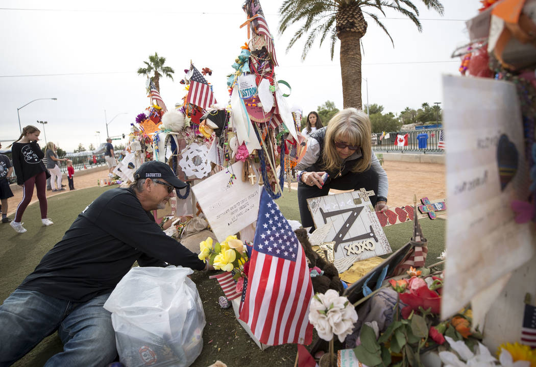 Chris and Debbie Davis, parents of Route 91 shooting victim Neysa Tonks, gather items from their daughter's cross following a cross-moving ceremony at a memorial for the victims at the Welcome to ...