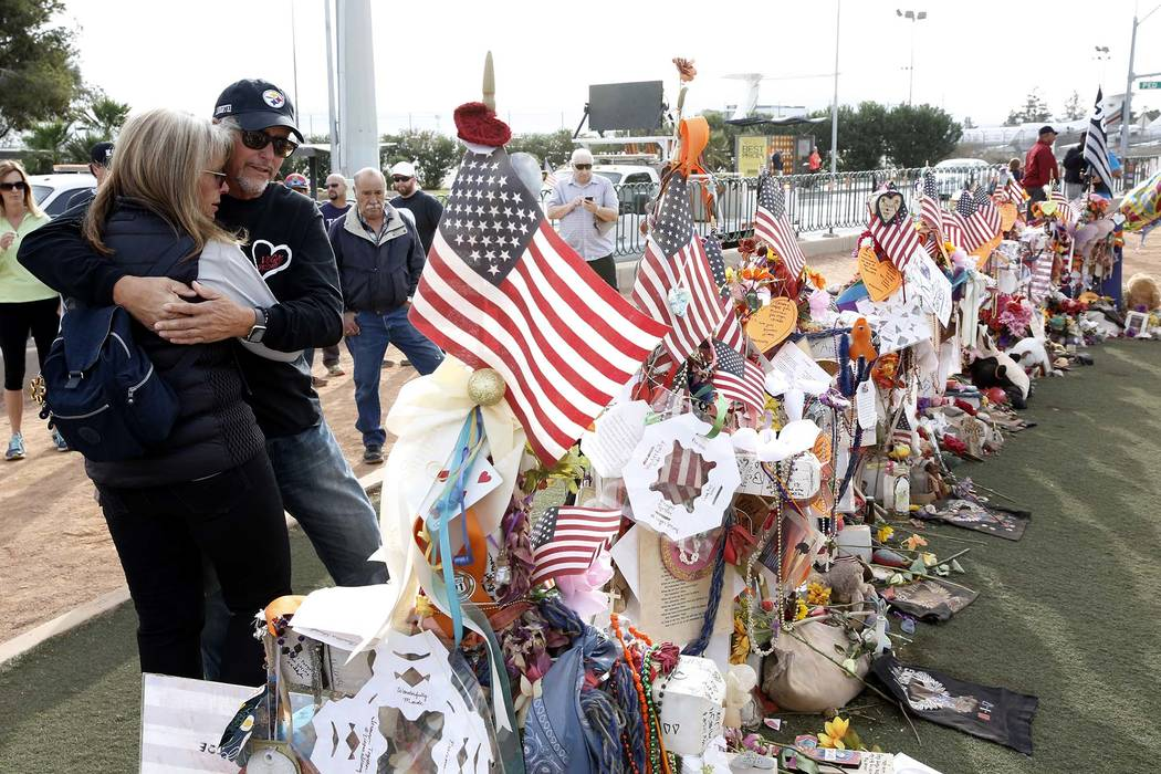 Chris Davis and his wife, Debbie, visit a memorial cross for their daughter Neysa Tonks at the Welcome to Fabulous Las Vegas sign Sunday, Nov. 12, 2017. Fifty-eight crosses and items that were ere ...