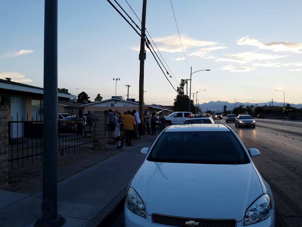 People gather along Lake Mead Boulevard outside an apartment complex at 825 W. Lake Mead Blvd. in Las Vegas on Tuesday, Aug. 21, 2018. Police were investigating a shooting that left one man dead. ...