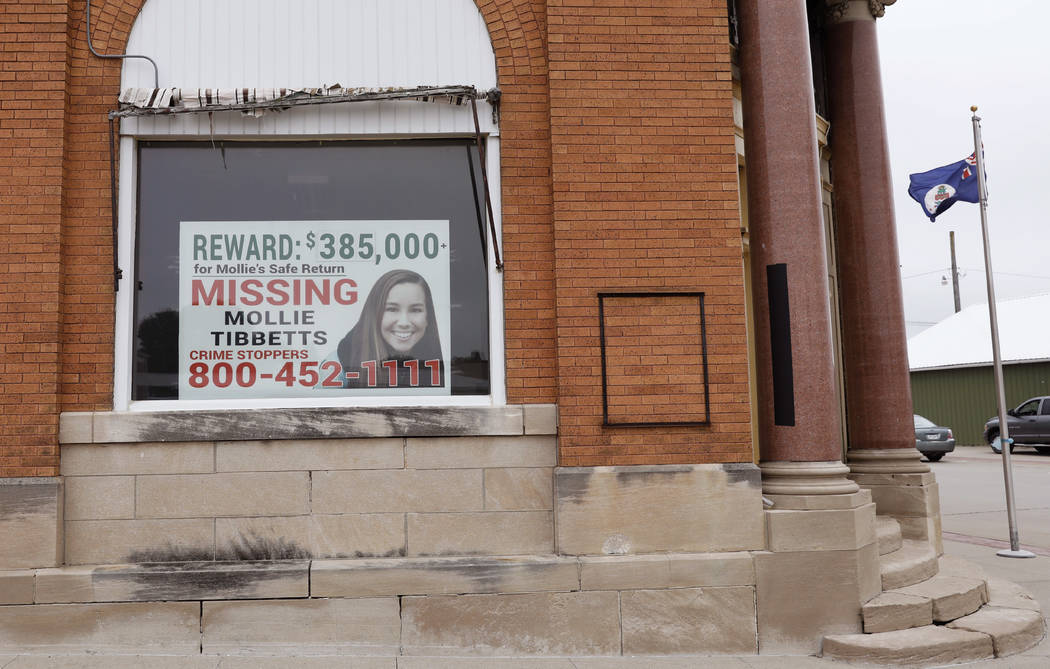 A poster for missing University of Iowa student Mollie Tibbetts hangs in the window of a local business, Tuesday, Aug. 21, 2018, in Brooklyn, Iowa. Tibbetts was reported missing from her hometown ...