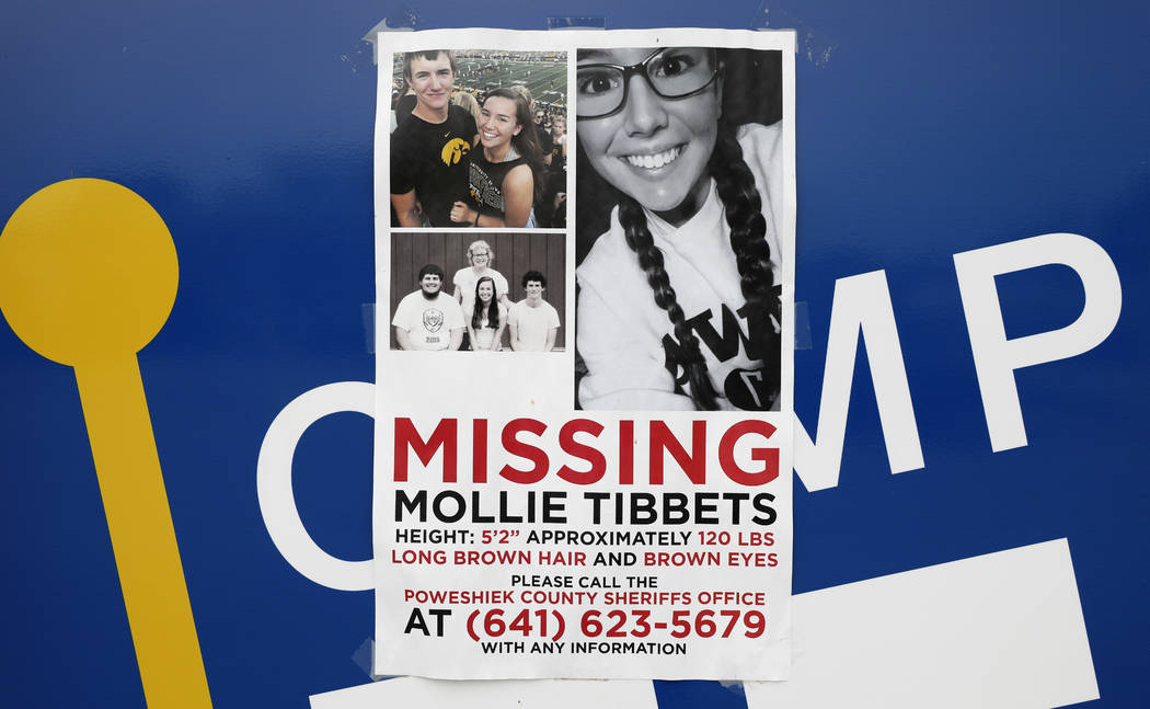 A poster for missing University of Iowa student Mollie Tibbetts hangs on the front door of a local business, Tuesday, Aug. 21, 2018, in Brooklyn, Iowa. (AP Photo/Charlie Neibergall)