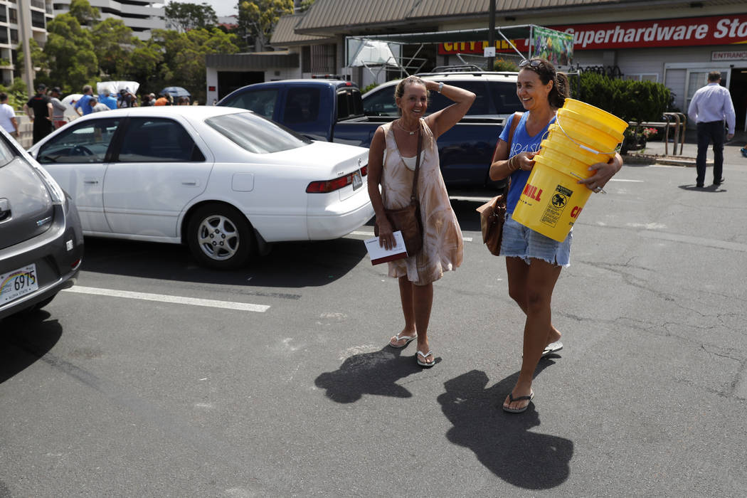 Aly Klein, right, and her mother Clarice Klein walks out of a local hardware store with several buckets of hurricane supplies, Wednesday, Aug. 22, 2018, in Honolulu. Hurricane Lane has weakened as ...