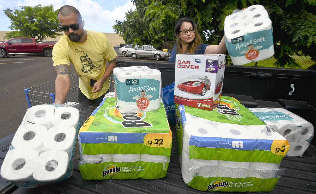 Bryce and Dom Boeder of Waimea, Kauai, load their truck with storm supplies in the parking lot of a Walmart store in Lihue, on the island of Kauai, Hawaii, Tuesday, Aug. 21, 2018. (Dennis Fujimoto ...