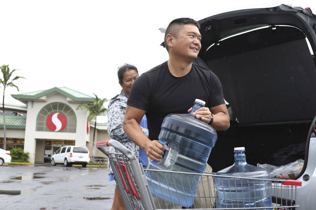Loren, right, and Ruby Aquino, of Honolulu, load water into their car ahead of Hurricane Lane, Wednesday, Aug. 22, 2018 in Honolulu. Hurricane Lane has weakened as it approaches Hawaii but was sti ...