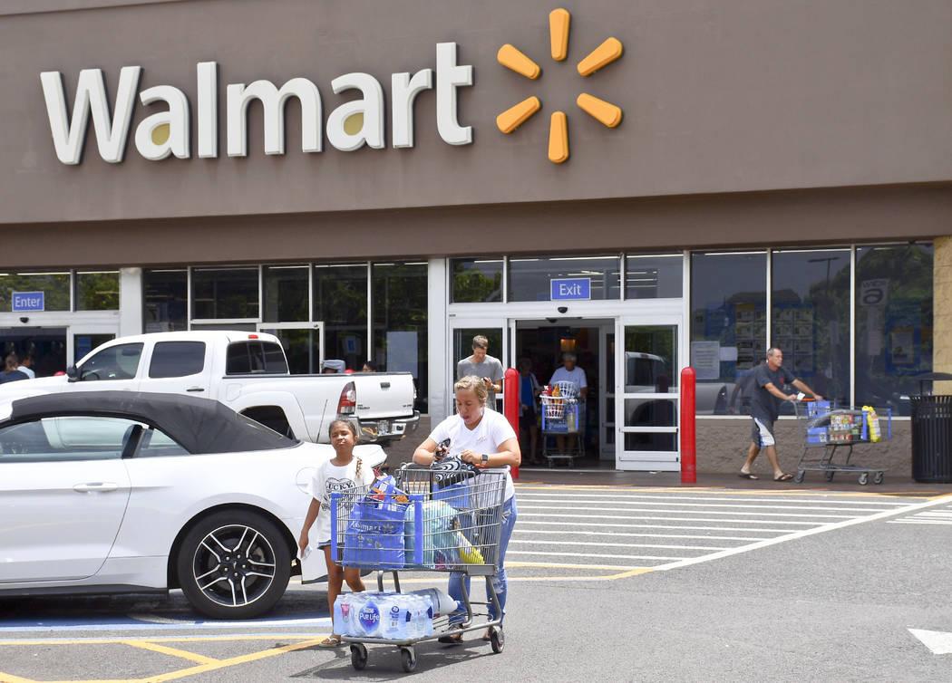 Taro and Taina Leong of Kekaha, Kauai, are among the customers leaving a Walmart store with supplies to prepare for Hurricane Lane, Tuesday, Aug. 21, 2018 in Lihue, on the island of Kauai, Hawaii. ...