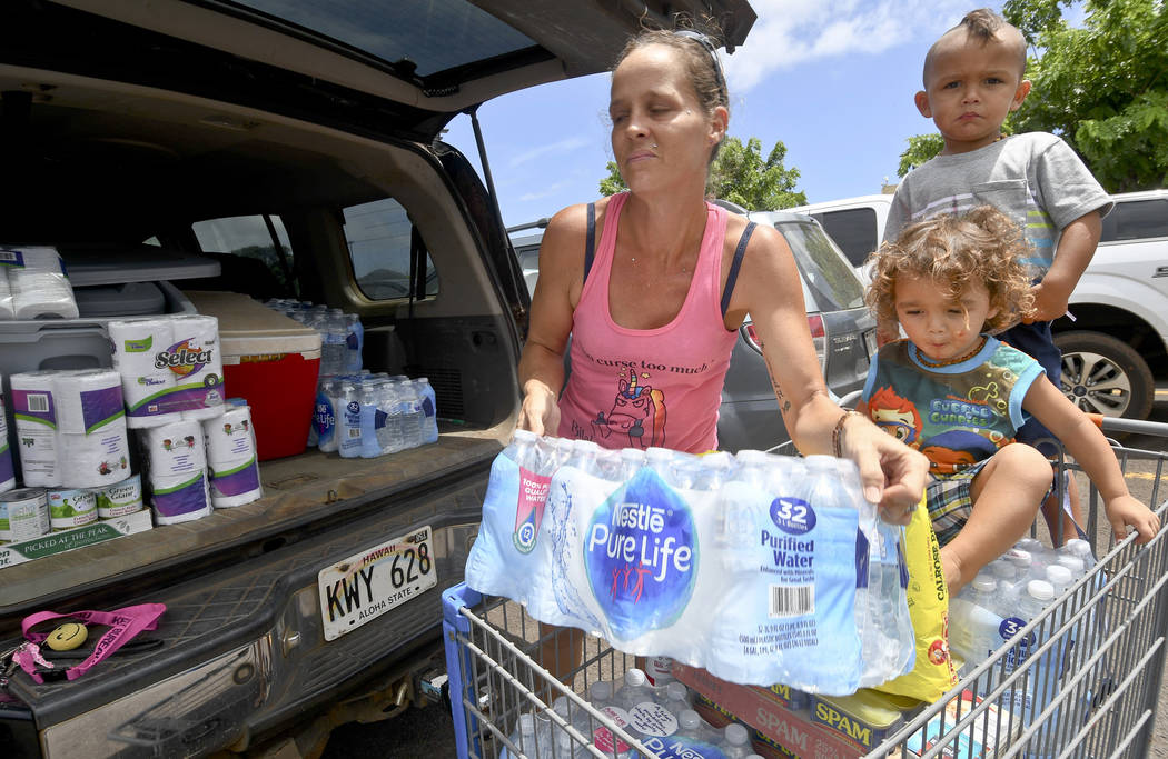 Brianna Sugimura unloads supplies for riding out the storm while her children, Radon-Kai and Kanaloa watch in the parking lot of a Walmart store Tuesday, Aug. 21, 2018, in Lihue, on the island of ...