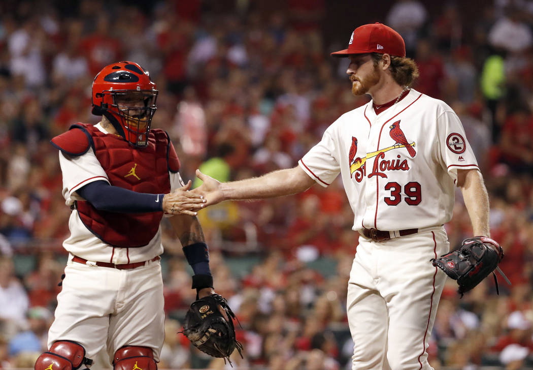 St. Louis Cardinals starting pitcher Miles Mikolas (39) is congratulated by catcher Yadier Molina after striking out Milwaukee Brewers' Eric Thames to end the top of the sixth inning of a baseball ...