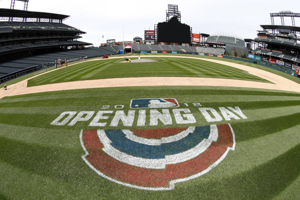 As viewed through a fisheye lens, a logo adorns the grass along the first-base line as grounds crew members prepare the field for the Colorado Rockies' regular-season home-opener Thursday, April 5 ...