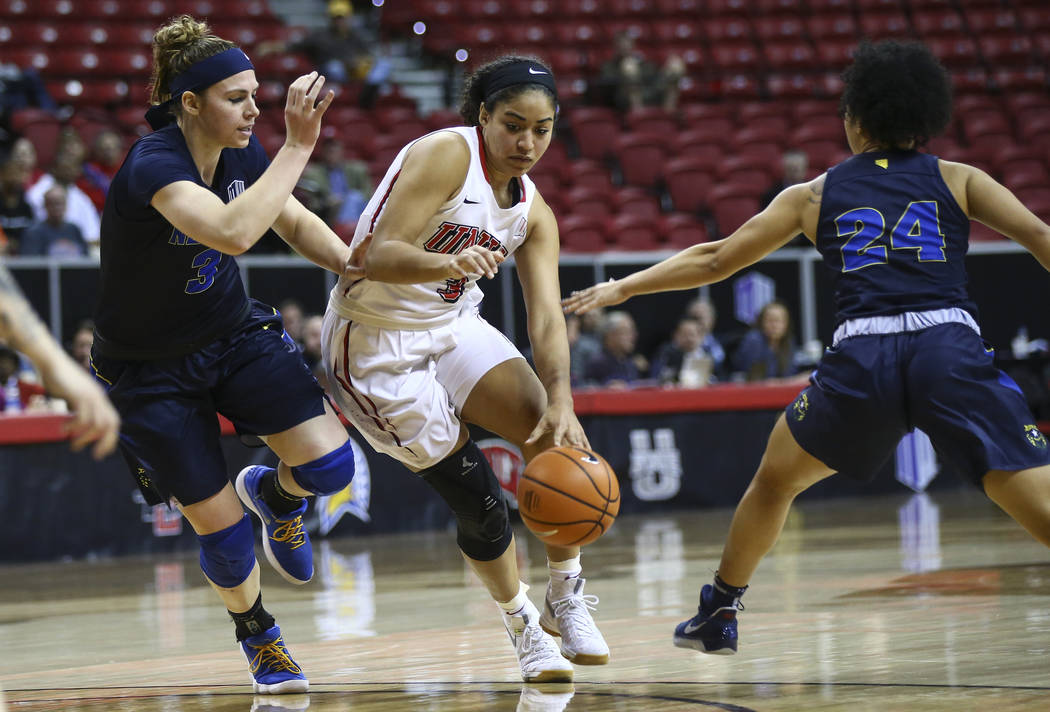 UNLV Lady Rebels forward/center Paris Strawther (3) drives as UNR Wolf Pack forward Teige Zeller (3) and guard Camariah King (24) defend during the second half of a basketball game in the Mountain ...