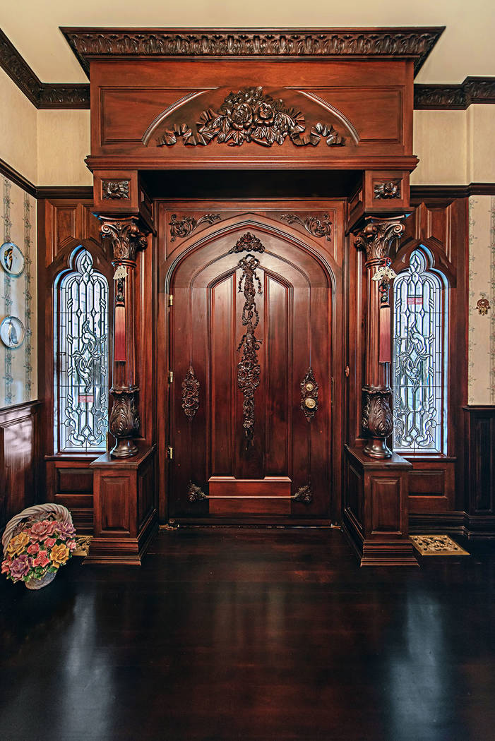 Rob Jensen Co. The front door is massive and made of handcarved mahogany flanked by stained-glass windows.