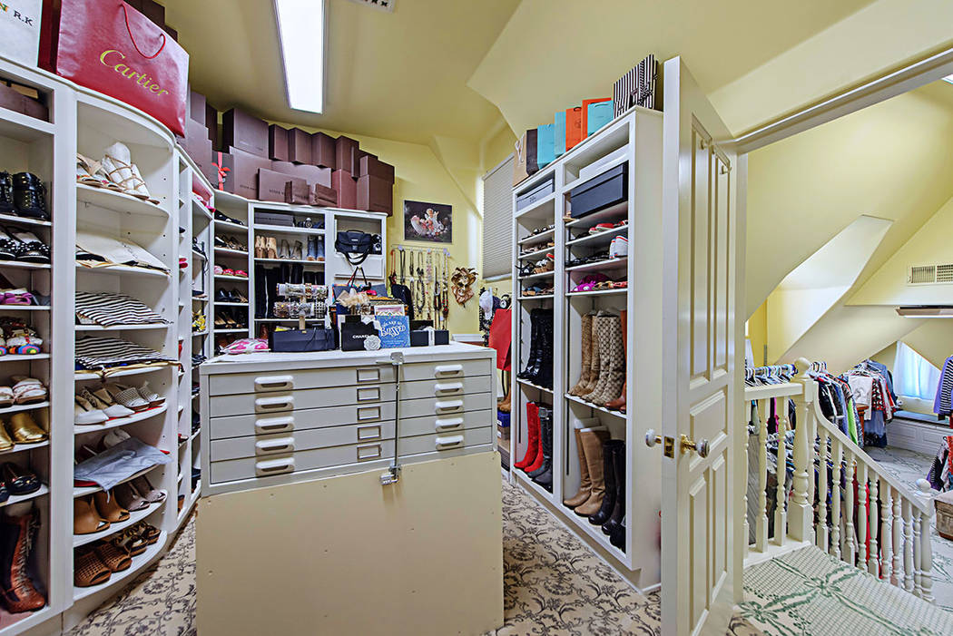 A massive walk-in closet features a separate area for shoes and handbags with stairs descending into a larger room for hanging clothes. (Rob Jensen Co.)