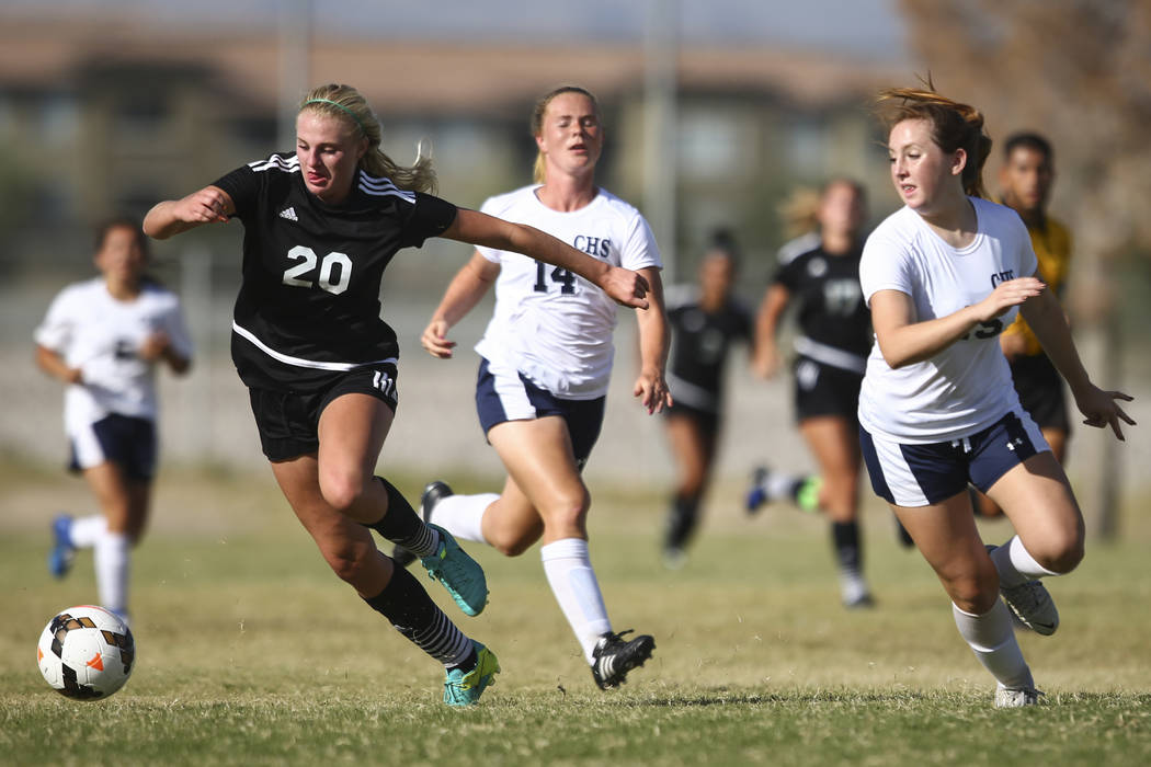 Palo Verde's Carlee Giammona (20) moves the ball up the field against Centennial's Dawn Madison Frederick (14) and Brooke Hawley (15) during a soccer game at Centennial High School in Las Vegas on ...