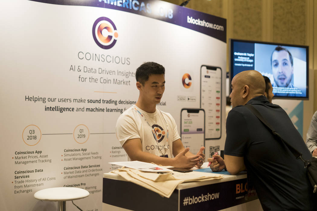 Daniel Jiwoong Im, CTO and co-founder of Coinscious, speaks to an attendee at Block Show at The Venetian in Las Vegas, Tuesday, Aug. 21, 2018. (Marcus Villagran/Las Vegas Review-Journal) @brokejou ...