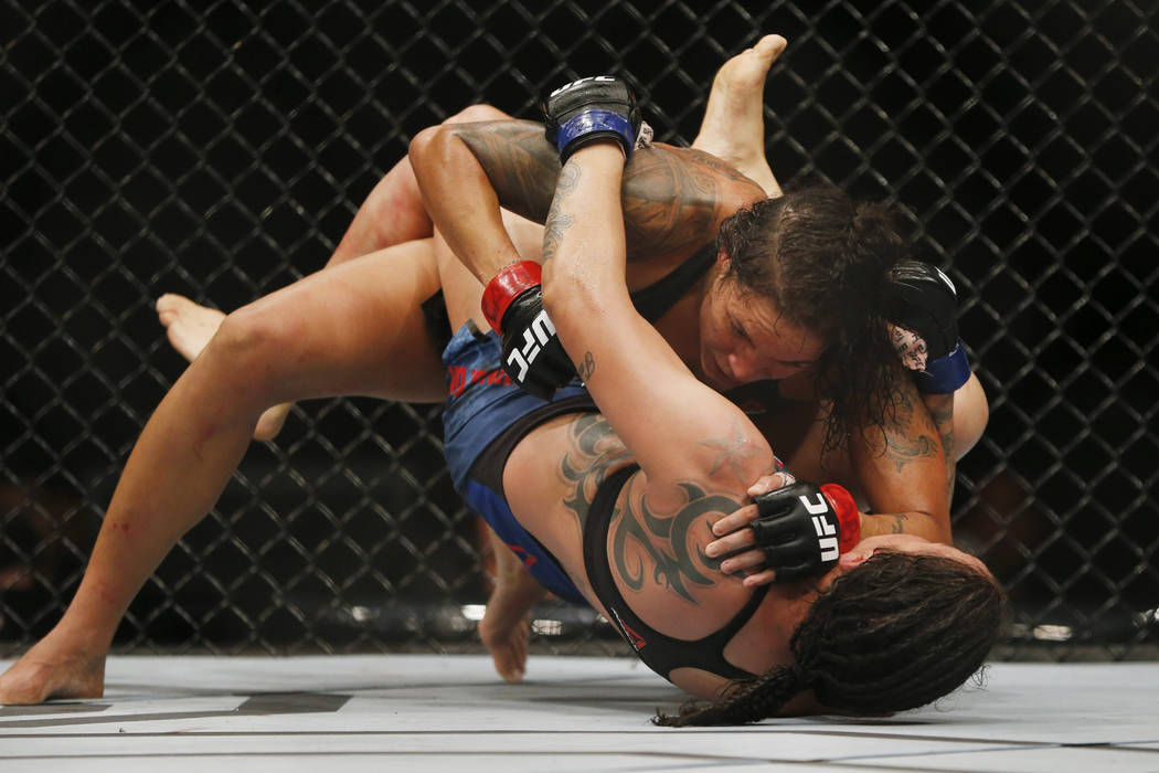 Amanda Nunes, top, from Brazil, fights Raquel Pennington, from the United States, during their UFC women's bantamweight mixed martial arts bout in Rio de Janeiro, Brazil, early Sunday, May 13, 201 ...