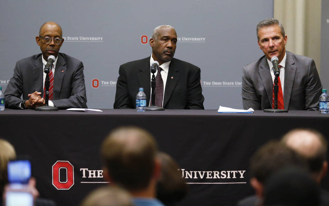 Ohio State football coach Urban Meyer, right, answers questions as athletic director Gene Smith and university President Michael Drake, left, listen during a news conference in Columbus, Ohio, Wed ...