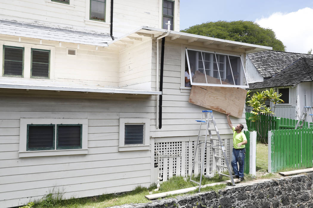 Contractor David Meyer, bottom, pushes a plywood board to Alecia Cone, left, and Craig Maromoto as they cover a window in preparation of the approaching strong winds expected from Hurricane Lane, ...